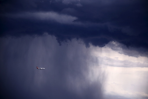 A Qantas Boeing 737-800 plane flies through heavy rain as a storm moves towards the city of Sydney, Australia