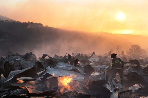 A firefighter removes the remains of a burned house on a hill, where more than 100 homes were burned due to forest fire but there have been no reports of death, local authorities said in Valparaiso, Chile