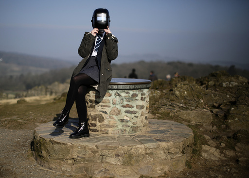 A girl uses a welding mask to view a partial solar eclipse from Bradgate Park in Newtown Linford