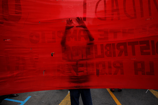 A supporter of the Communist party uses a scissors to make holes on a banner as he takes part in a May Day rally in Malaga