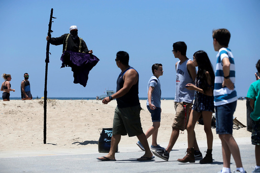 People watch a street performer in the Venice neighborhood of Los Angeles