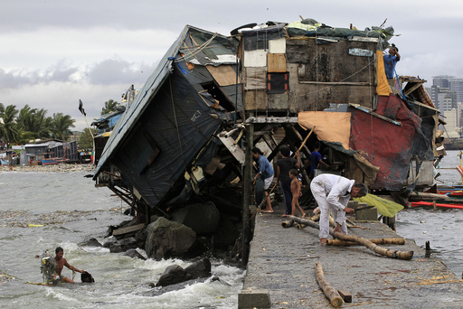 People work around damaged house along coastal area after strong winds brought by Typhoon Rammasun battered the Baseco compound
