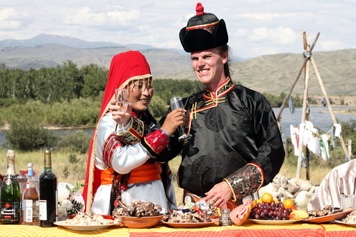 Quirk, of U.S., and his bride Ondar toast champagne during their wedding ceremony outside the city of Kyzyl, in the Russia's Tuva region