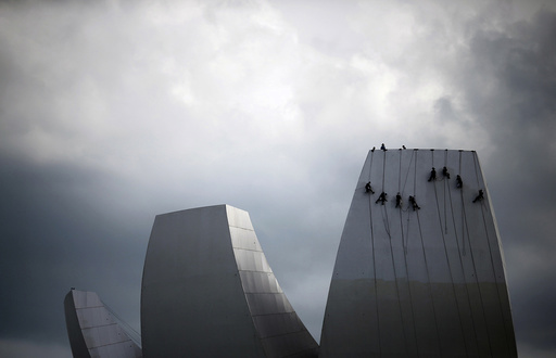 Cleaners rope down as they wash the facade of the ArtScience Museum in Singapore