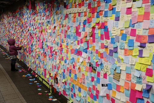 A young girl adds a message written on a post-it note to a display that was started in reaction to the election of President-elect Donald Trump in New York