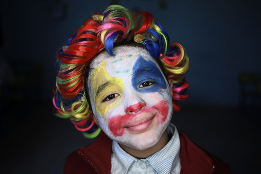 A boy with clown make up poses for a picture during Children's Day celebrations, at a school in Benghazi