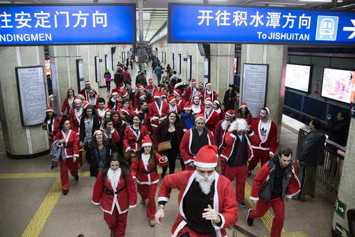Participants dressed in Santa Claus costumes leave at a subway station to attend the SantaCon in Beijing