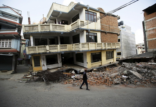 A man walks past a damaged and collapsed five-storey house, a month after the April 25 earthquake in Kathmandu