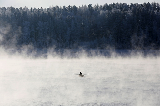 A man rows a boat through a frosty fog along the Yenisei River at air temperature some minus 20 degrees Celsius in the Taiga district outside the Siberian city of Krasnoyarsk, Russia