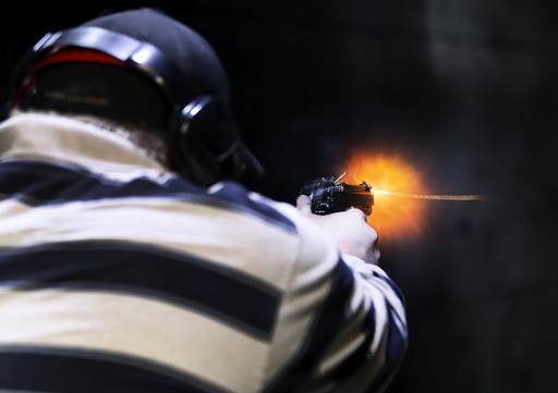 A man fires a Sig P320 handgun at the Ringmasters of Utah gun range, in Springville, Utah