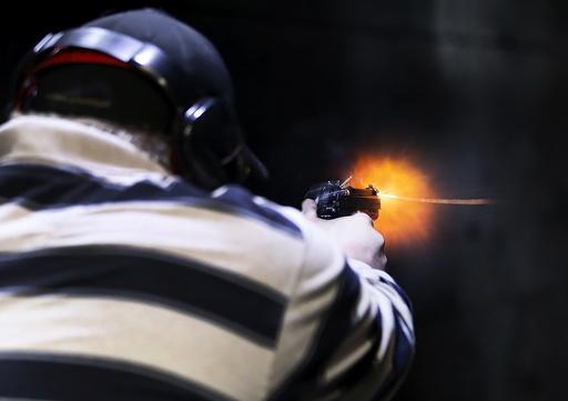 A man fires a Sig P320 handgun at the Ringmasters of Utah gun range, in Springville, Utah