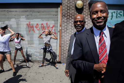 Republican presidential hopeful Ben Carson stops on the street to watch the Marching Cobras perform as he tours the Harlem area of New York.