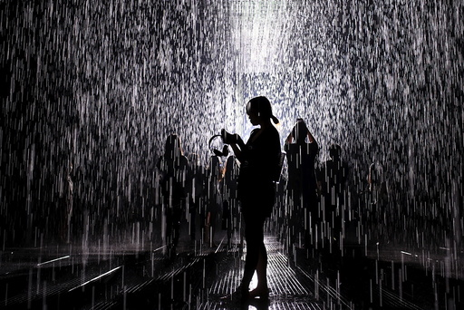 People visit the Rain Room, an installation by Random International, at a museum in Shanghai