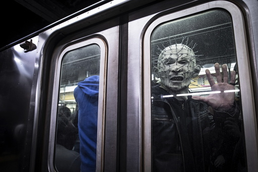 A man dressed up as Pinhead from the Hellraiser series poses for a photo as his subway train pulls away at Times Square station in Manhattan