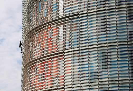 French climber Alain Robert, also known as The French Spiderman, scales the 38-story skyscraper Torre Agbar in Barcelona