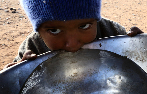 Stateless Arab boy from an ethnic group known as Bedoon, who are believed to be descendants of nomadic Bedouins, drinks water from a pot in a desert west of Al-Jawf region