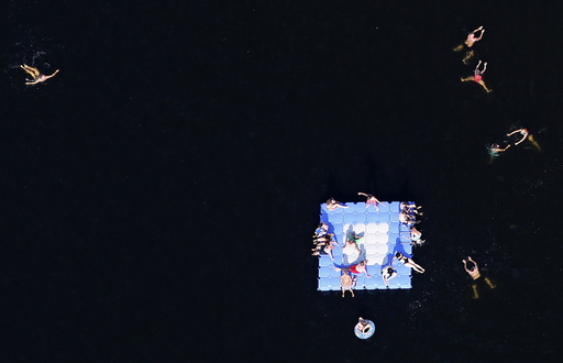 An aerial view shows people relaxing on a floating platform at Silbersee lake on a hot summer day in Haltern