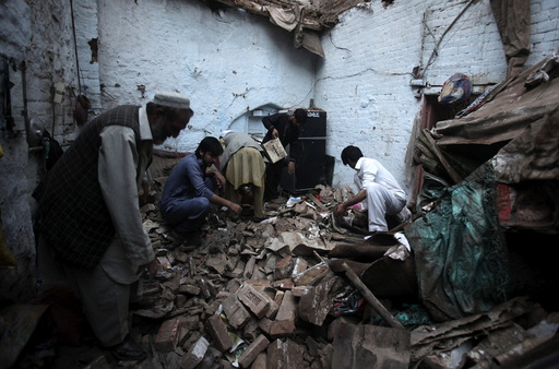Residents search for belongings in the rubbles of a house after it was damaged by an earthquake in Peshawar