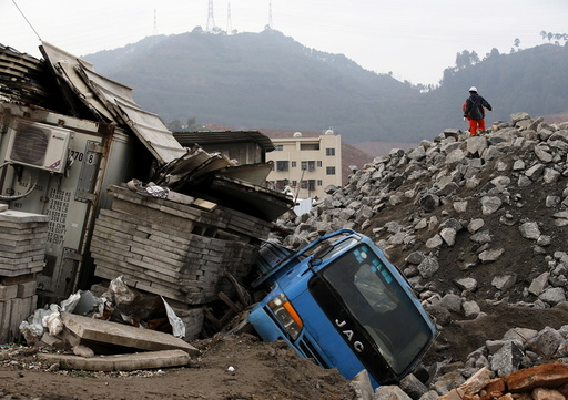 Rescue workers walk past a damaged vehicle in the industrial park hit by a landslide in Shenzhen
