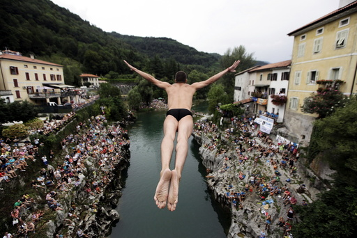 Competitor jumps from the old bridge during a cliff diving competition in Kanal ob Soci