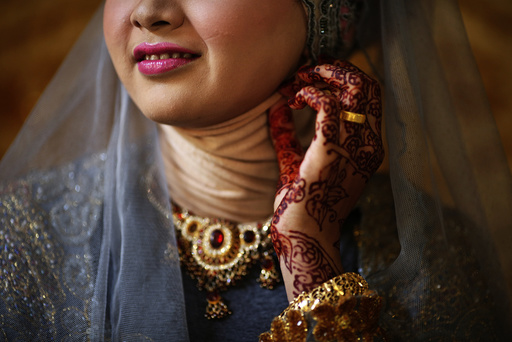 Winda Wahyuni adjusts her traditional clothes as she waits for her future husband to arrive for their wedding in Banda Aceh
