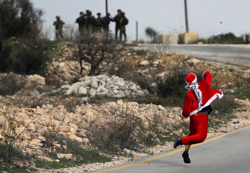 Palestinian demonstrator dressed as Santa Claus hurls stones towards Israeli troops during clashes at a protest near the West Bank city of Ramallah