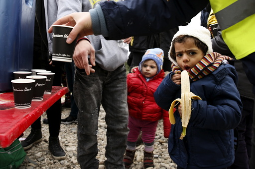 A migrant child eats a banana as hot drinks are distributed moments after the arrival of a rubber dinghy packed with refugees and migrants on a beach on the Greek island of Lesbos