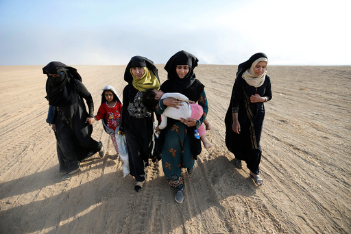 Civilians return to their village after it was liberated from Islamic State militants, south of Mosul