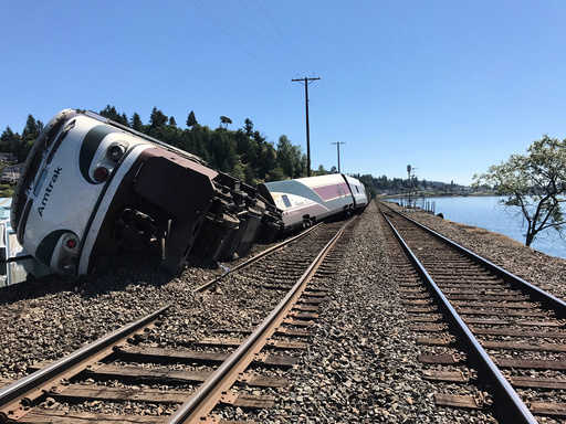 A derailed Amtrak passenger train lies on its side before the Chambers Bay Bridge on Puget Sound in Steilacoom