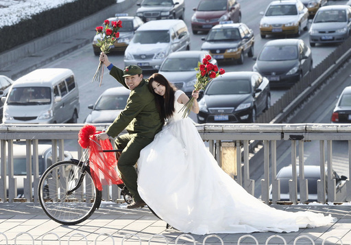 An engaged couple sit on a bicycle as they pose for wedding photographs to the theme of