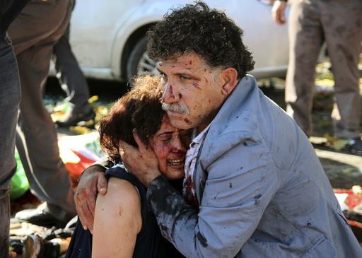An injured man hugs an injured woman after an explosion during a peace march in Ankara