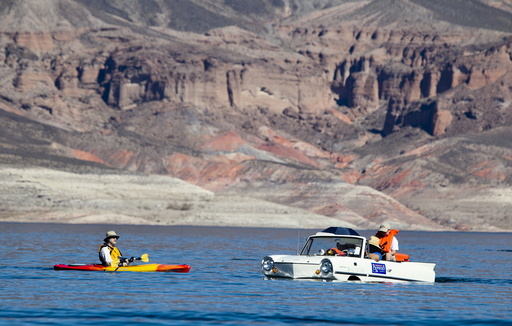 A kayaker looks over a 1965 Amphicar, driven by Dean Baker of Lake Havasu, Arizona, during the first Las Vegas Amphicar Swim-in at Lake Mead near Las Vegas