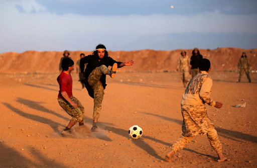 Free Syrian Army fighters play soccer in the northern Syrian town of al-Rai