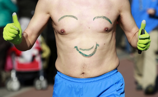 A participant gestures while running in the Half-Naked Marathon at Olympic Forest park in Beijing