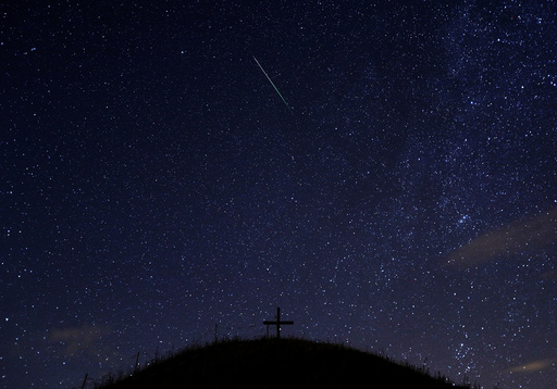 A meteor streaks past stars in the night sky above Leeberg hill during the Perseid meteor shower in Grossmugl