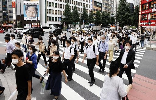 Folk krysser en gate i Tokyo. De aller fleste bærer munnbind for å hindre smittespredning. Foto: Kyodo News via AP / NTB scanpix