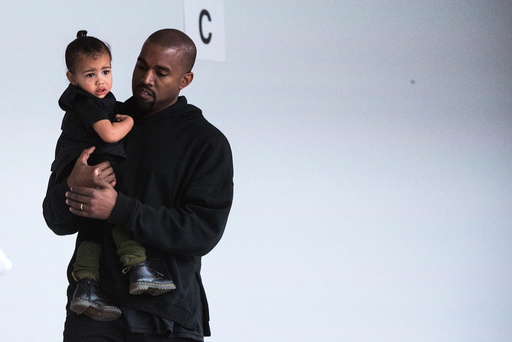 Kanye West carries his daughter, North, while preparing for a presentation of his Fall/Winter 2015 partnership with Adidas at New York Fashion Week