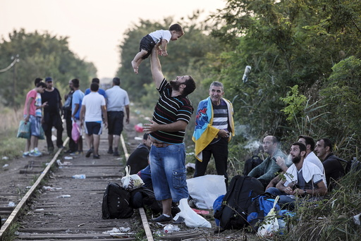 A migrant, hoping to cross into Hungary, plays with a child along a railway track outside the village of Horgos in Serbia, towards the border it shares with Hungary
