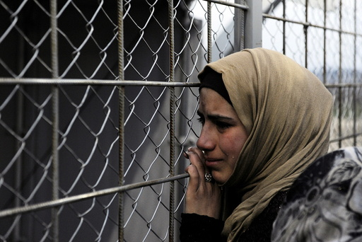 A refugee cries next to the border fence of the Greek-Macedonian borderas during a protest by stranded refugees who wait for the border crossing to reopen near the Greek village of Idomeni