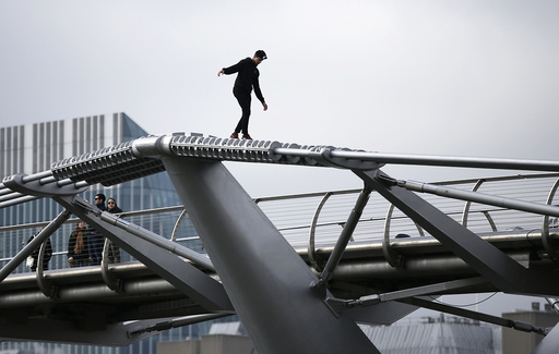 A man balances as he walks on the support structure of the Millennium Bridge in London