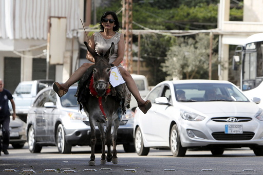 A woman rides a donkey during a donkey race in Roum village