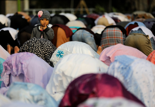 People attend prayers for the Muslim holiday of Eid Al-Adha on a street outside of a mosque in Jakarta