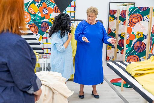 Statsminister Erna Solberg fikk prøve en nylig sydd smittevernsfrakk da hun besøkte den nyåpnede systua på Ikea Furset i Oslo. Systua drives av Sisters in business og ansetter personer som tidligere har stått utenfor arbeidslivet. Foto: Tore Meek / NTB scanpix