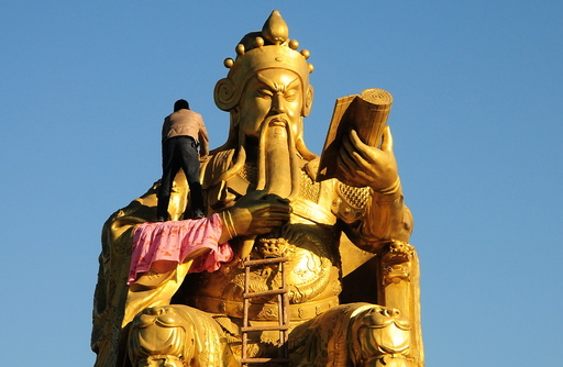 A worker paints as he repairs a bronze statue of a Guan Yu, a Chinese historical figure, in Nanyang