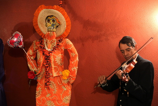 Musician plays his violin next to a depiction of La Santa Muerte (Saint Death) at a shrine during Day of the Dead celebrations in Ciudad Juarez
