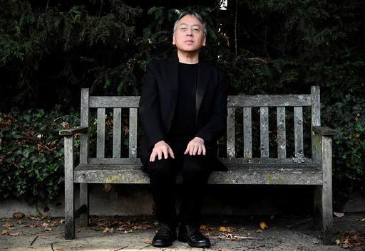 Author Kazuo Ishiguro poses for the media outside his home, following the announcement that he has won the Nobel Prize for Literature, in London