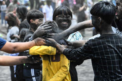 People smear black ash with hands onto each other during Monihei Carnival in Puer