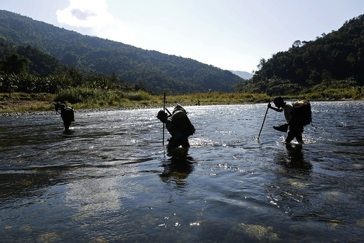 Naga men walk though a creek during a hunting trip between Donhe and Lahe township in the Naga Self-Administered Zone
