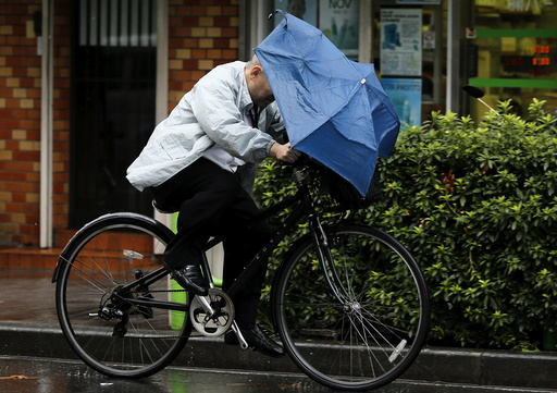 A man holding onto an umbrella as he cycles in heavy rain caused by typhoon Etau in Tokyo's business district
