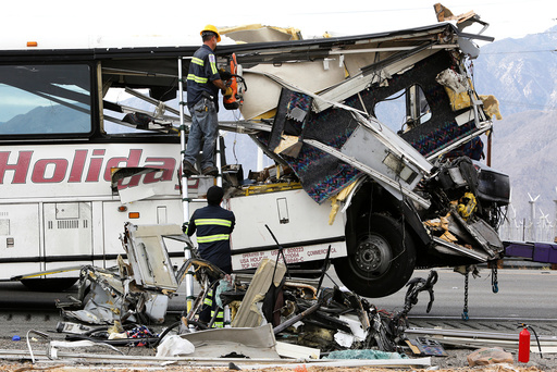 Workers cut away debris from the front of a bus involved in a mass casualty crash on the westbound Interstate 10 freeway near Palm Springs, California